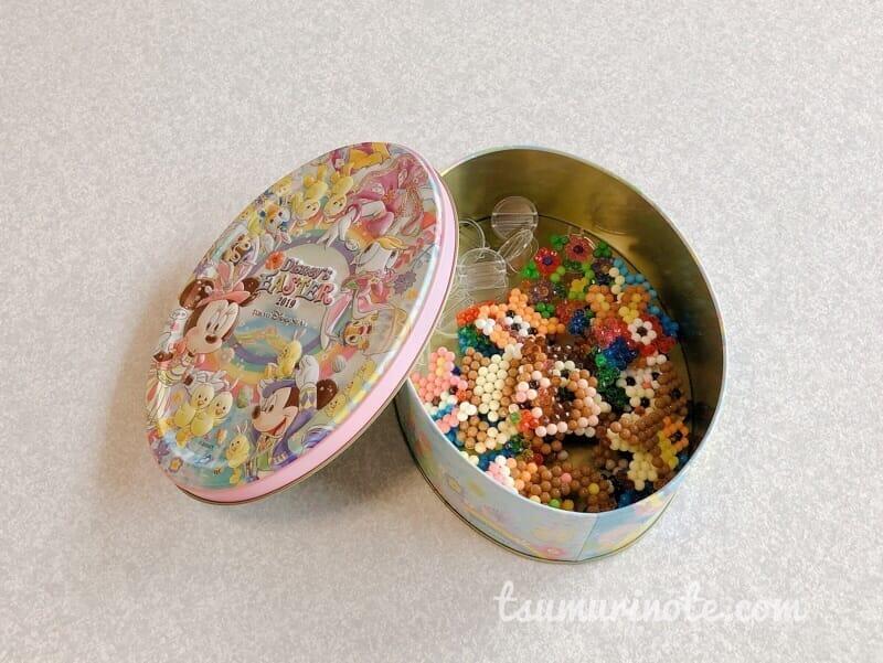 アクアビーで作った作品をお菓子の缶に詰めた図